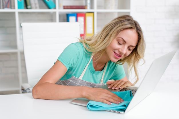 Lächelnder hübscher frauenreinigungslaptop mit blauem gewebe auf weißem schreibtisch