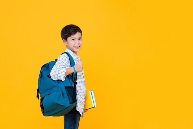 Lächelnder hübscher gemischter schuljunge mit büchern und rucksack, der daumen auf lokalisierter gelber wand mit kopienraum aufgibt