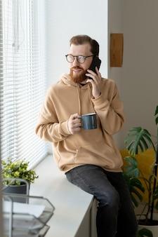 Lächelnder hübscher junger bärtiger mann im kapuzenpulli, der auf fensterbank sitzt und kaffee trinkt, während auf handy spricht