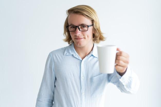 Lächelnder hübscher junger mann, der becher tee anhebt