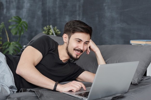 Lächelnder hübscher junger mann, der im bett liegt und laptop verwendet, während mit freunden wetteifern, wetteifern online-app