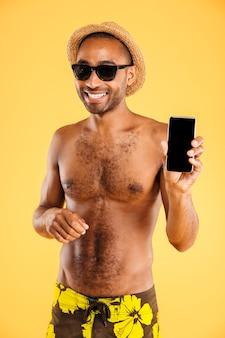Lächelnder hübscher junger mann im hut und in der sonnenbrille, die smartphone des leeren bildschirms über orange wand halten