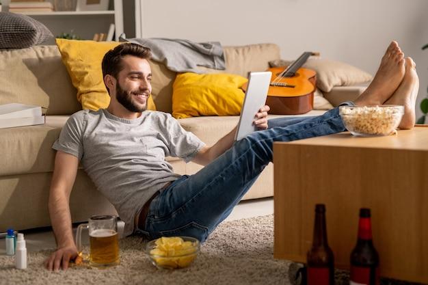 Lächelnder hübscher junger mann in der freizeitkleidung, die mit füßen auf kaffeetisch sitzt und mit freunden online zu hause isolation plaudert