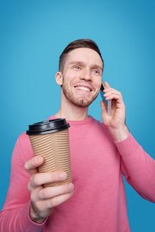 Lächelnder hübscher junger mann mit stoppeln, die kaffee vom takeout-becher trinken und durch handy plaudern