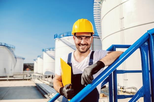 Lächelnder hübscher kaukasischer arbeiter insgesamt und mit helm auf kopf, der sich auf das geländer stützt und ordner mit dokumenten hält. ölproduktion.