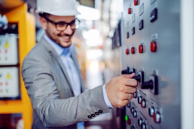 Lächelnder hübscher kaukasischer aufseher im grauen anzug und mit dem helm auf kopf, der schalter einschaltet. selektiver fokus zur hand. kraftwerksinnenraum.