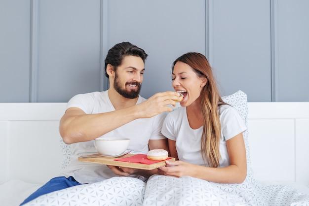 Lächelnder hübscher kaukasischer bärtiger mann, der seine schöne freundin mit donut füttert, während er im bett im schlafzimmer sitzt. morgens.