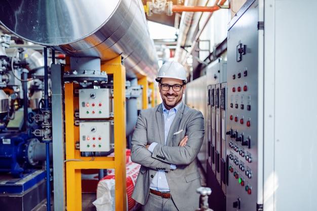 Lächelnder hübscher kaukasischer geschäftsmann im grauen anzug und mit helm auf kopf stehend mit verschränkten armen neben armaturenbrett. kraftwerksinnenraum.