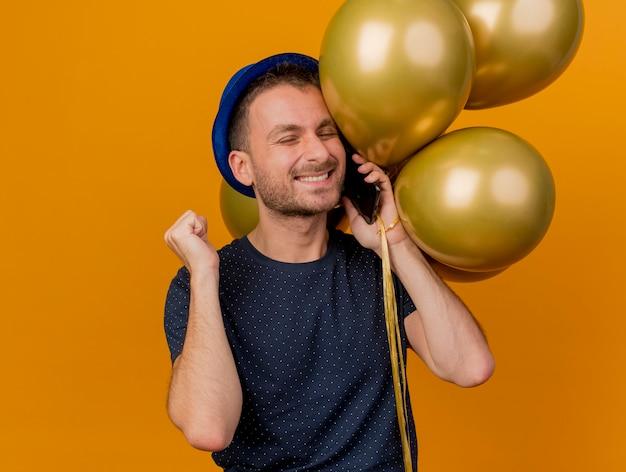 Lächelnder hübscher kaukasischer mann, der blauen parteihut trägt, hält faust und hält heliumballons, die am telefon sprechen, lokalisiert auf orange hintergrund mit kopienraum