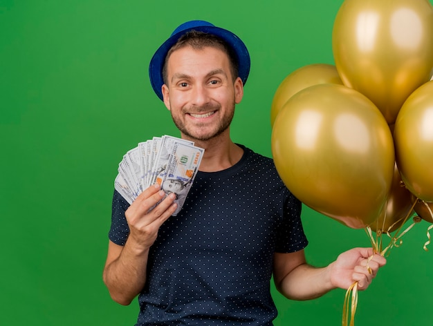 Lächelnder hübscher kaukasischer mann, der blauen parteihut trägt, hält geld und heliumballons lokalisiert auf grünem hintergrund mit kopienraum
