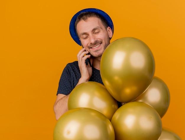 Lächelnder hübscher kaukasischer mann, der blauen parteihut trägt, hält heliumballons, die auf telefon lokalisiert auf orange hintergrund mit kopienraum sprechen