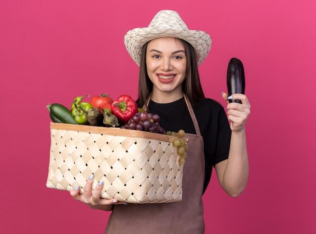 Lächelnder hübscher kaukasischer weiblicher gärtner, der gartenhut hält, der gemüsekorb und aubergine auf rosa hält
