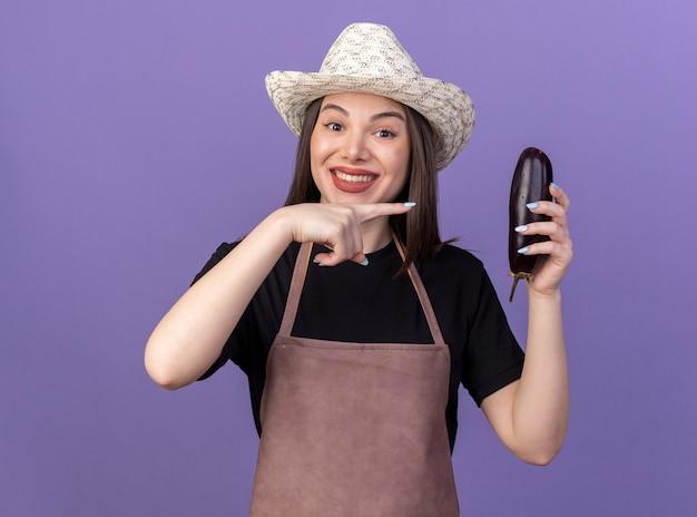 Lächelnder hübscher kaukasischer weiblicher gärtner, der gartenhut hält und auf aubergine auf purpur zeigt