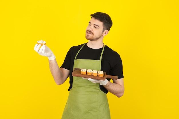 Lächelnder hübscher kerl, der kuchenrolle auf einem gelb betrachtet.