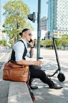 Lächelnder hübscher mann, der auf brüstung sitzt, herausnehmen trinkt und mit kollegen am telefon spricht