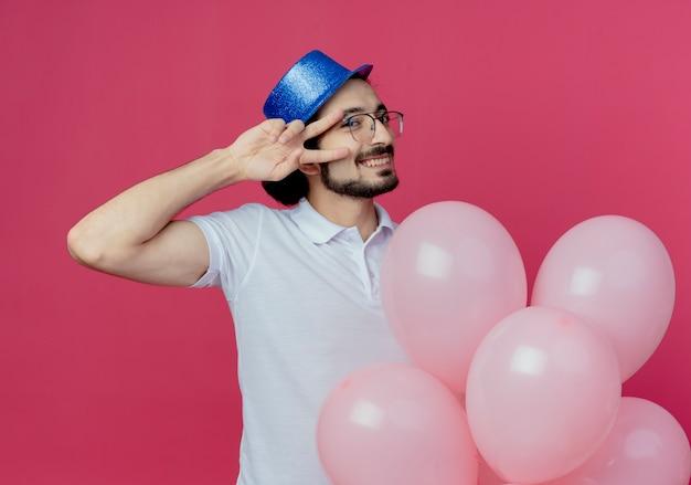 Lächelnder hübscher mann, der brille und blauen hut trägt, der ballons hält und friedensgeste lokalisiert auf rosa hintergrund zeigt