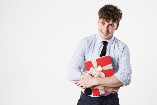 Lächelnder hübscher mann mit einer geschenkbox