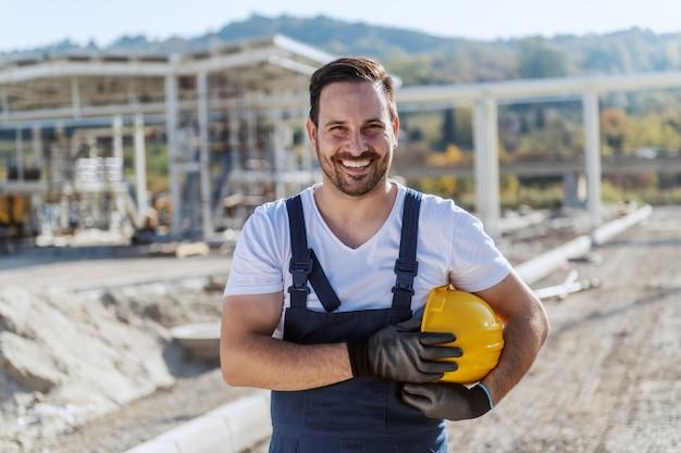 Lächelnder hübscher unrasierter kaukasischer arbeiter im gesamtstand an der raffinerie mit helm unter achselhöhle