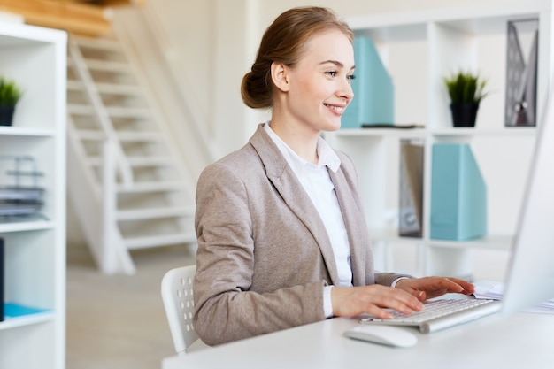 Lächelnder hübscher unternehmer bei der arbeit