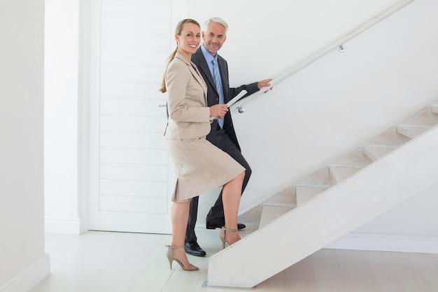 Lächelnder immobilienmakler, der dem möglichen käufer treppe zeigt