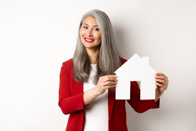 Lächelnder immobilienmakler, der papierhaus-zwischenablage zeigt, makler, der mit kunden arbeitet und über weißem hintergrund steht.