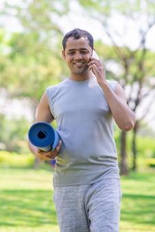 Lächelnder indischer kerl, der am telefon auf seiner methode zur yogaklasse spricht.