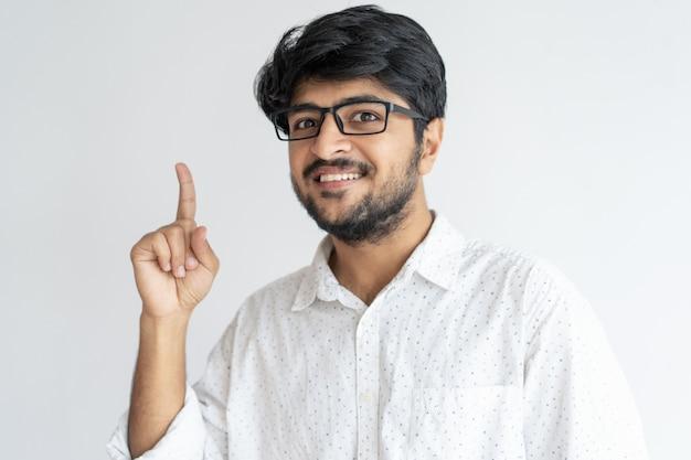 Lächelnder indischer kerl, der aufwärts zeigt und kamera betrachtet