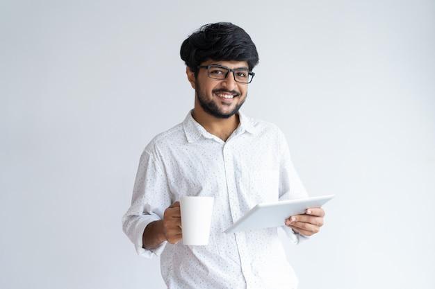 Lächelnder indischer mann, der becher und tablet-computer hält und kamera betrachtet.