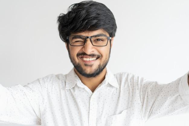 Lächelnder indischer mann, der selfie foto blinzelt und macht