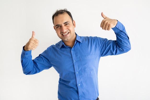 Lächelnder indischer mann, der sich beide daumen zeigt