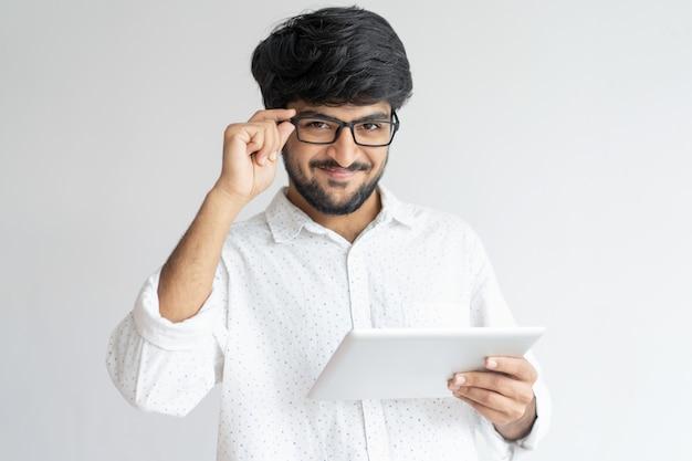 Lächelnder indischer mann, der tablet-computer verwendet und gläser justiert