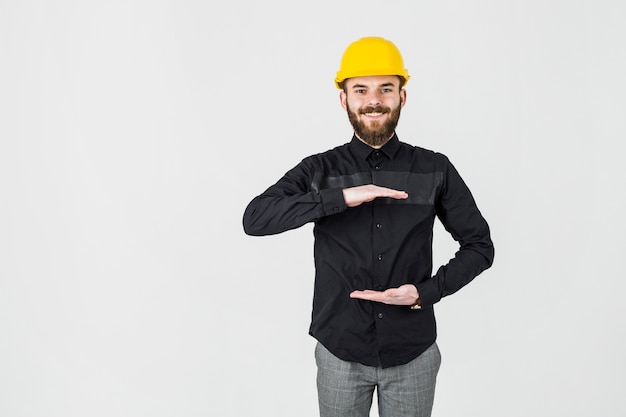 Lächelnder ingenieur, der das gelbe hardhatgestikulieren trägt
