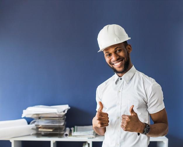 Lächelnder ingenieur, der den weißen hardhat zeigt daumenzeichen trägt