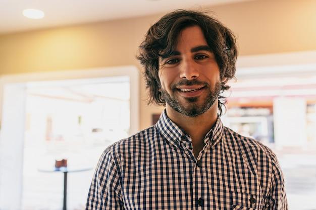Lächelnder inneninnen des jungen gutaussehenden mannes, der ein hemd trägt.