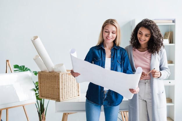 Lächelnder intelligenter frauendesigner, der ausgerolltes papier demonstriert