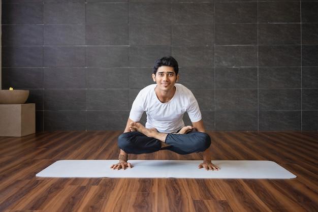 Lächelnder jogi, der skalenyogahaltung in der turnhalle tut