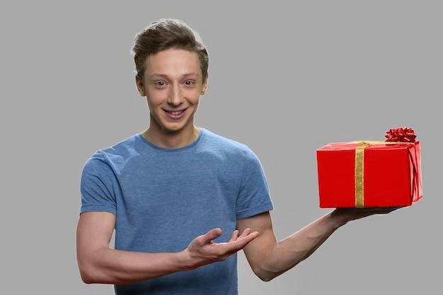 Lächelnder jugendlich junge, der auf geschenkbox in seiner hand zeigt. hübscher jugendlich kerl, der geschenkbox gegen grauen hintergrund anbietet.