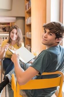 Lächelnder jugendlich junge mit dem buch, das nahe freundin sitzt