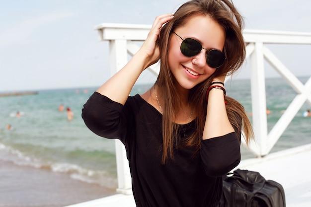 Lächelnder jugendlicher an der pier aufwirft