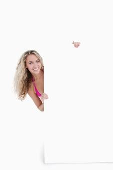 Lächelnder jugendlicher, der ihren körper hinter einem leeren plakat versteckt