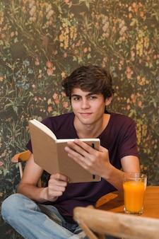 Lächelnder jugendlicher, der im café liest