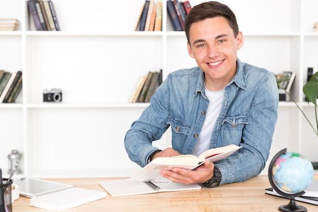 Lächelnder jugendlicher, der im klassenzimmer studiert