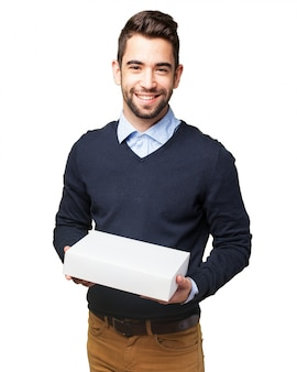 Lächelnder jugendlicher mit einem paket aufwirft