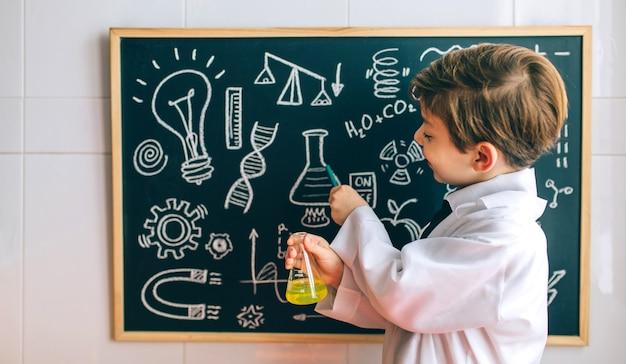 Lächelnder junge, der als chemiker verkleidet ist, mit einer flasche, die auf eine tafel mit zeichnungen zeigt