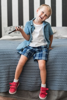 Lächelnder junge, der auf dem bett hält intelligentes telefon sitzt