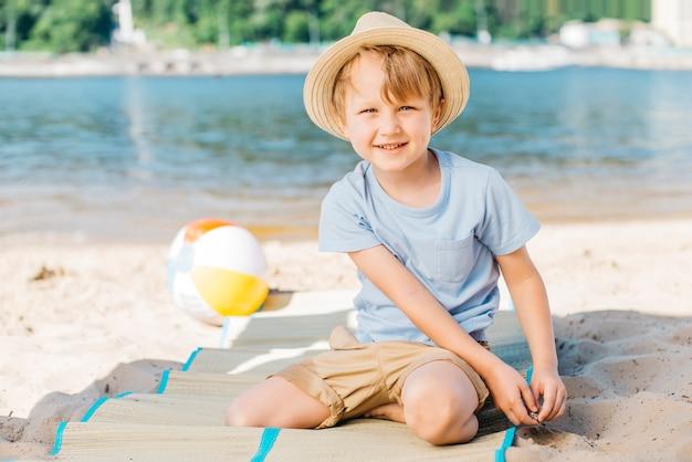 Lächelnder junge, der auf matte auf sandufer sitzt