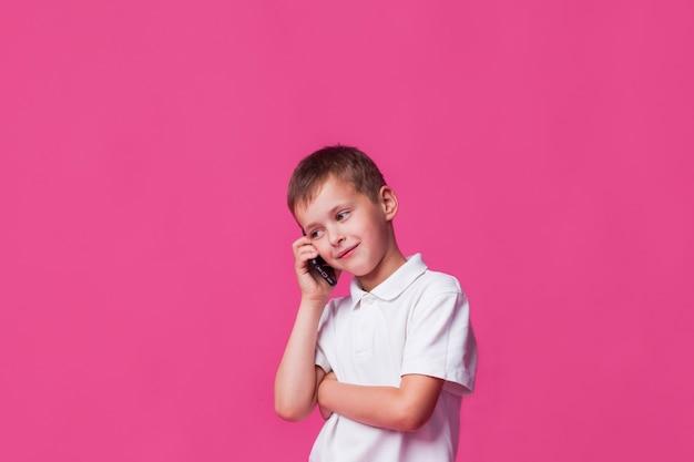 Lächelnder junge, der auf mobiltelefon über rosa wandhintergrund spricht