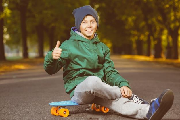 Lächelnder junge, der auf penny board sitzt
