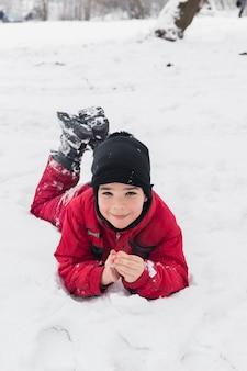 Lächelnder junge, der auf schneebedeckter landschaft liegt
