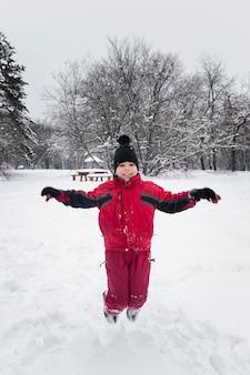 Lächelnder junge, der auf schneebedecktes land in der wintersaison springt